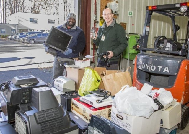 This is a picture of two gentlemen holding different types of e-waste. The guy on the left is smiling and holding a laptop while the guy on the right is smiling and holding a phone and cord. There are boxes of e-waste on the ground in front of them.