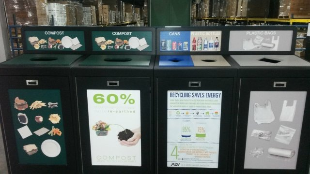 This is a picture of four different compost and recycling bins lined in a row, adjacent to each other. Each are labled with words and pictures. From left to right, there are two compost bins, a bin for cans and plastic bottles, and one for plastic bags.