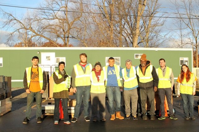 This is a picture of volunteers standing in a horizontal line, posing for a picture. They're wear lime green reflecting vests and standing in front of a green, one-story building and leafless trees.