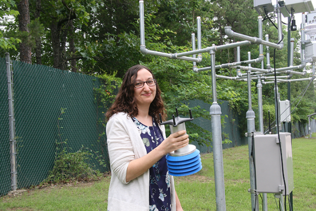 EPA Scientist Ingrid George holds an SPod, a fenceline monitoring system developed by EPA that can identify air pollution plumes from leaks or other fugitive emissions at the perimeter of an industrial facilities.