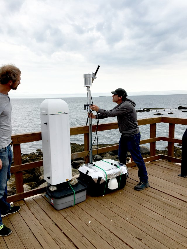 David Williams and Luke Valin (from NERL) at the U.S. Fish and Wildlife Service Outer Island, CT site. Dave is installing a spectrometer and the large white instrument is a ceilometer.