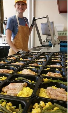 This is a picture of a kitchen worker filling containers of meals to be donated.