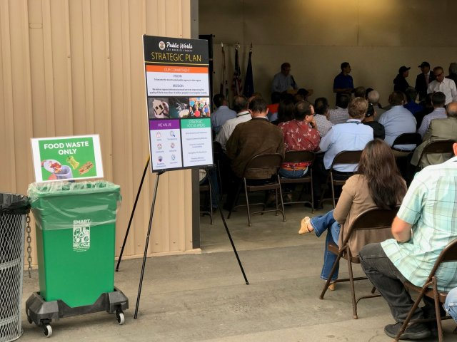 This is a meeting with rows of people attending with a food waste bin next to a Public Works strategy sign.