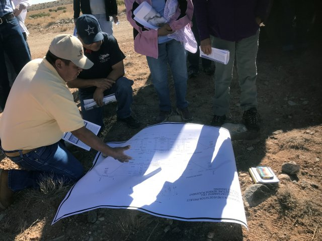 Diné Uranium Remediation Advisory Commissioners review engineering drawings of reclamation work performed by the Navajo Abandoned Mine Lands Program