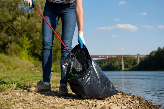 Picture of a volunteer picking up plastic litter on the coast of a river clean-up project.