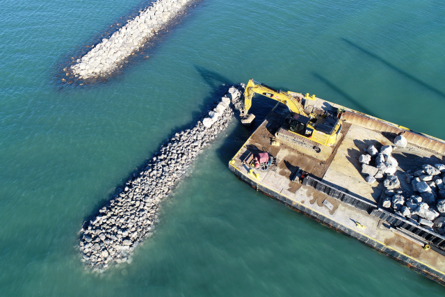 Photo of A barge places rocks along a berm constructed to reduce erosion and provide additional spawning habitat within the Detroit RI AOC. Photo Credit: Friends of the Detroit River