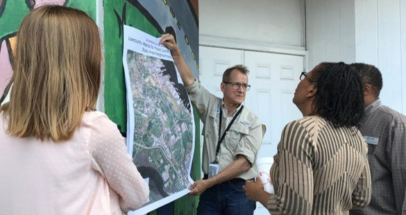A group of EPA researchers and community members review a map of a port