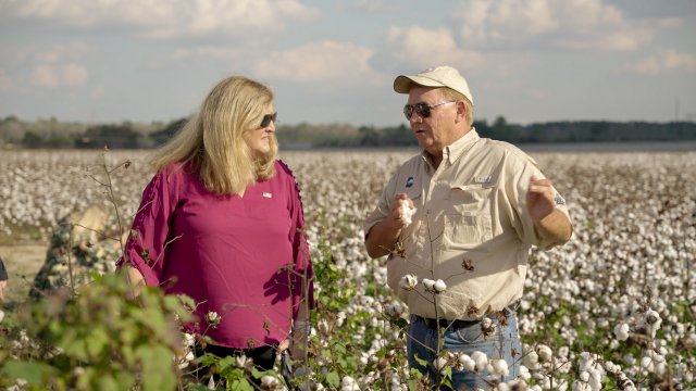 photo of Dunn and a man outstanding in his field