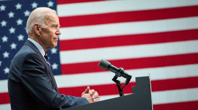President Biden standing at a lectern in front of an American flag backgdrop.