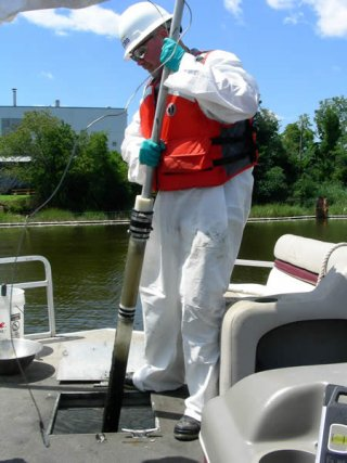 Collecting sediment samples with a push core sampler.
