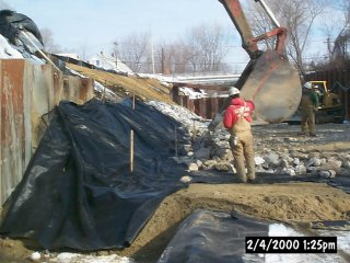 [February 4, 2000] Cell C - Backfill of sediments/banks adjacent to permanent, source control sheetpile. Bottom geotextile, sand, top geotextile, and rip-rap layers visible.