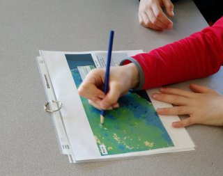 Child points at EnviroAtlas map, watershed lesson
