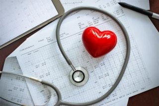 Heart and stethoscope on top of papers