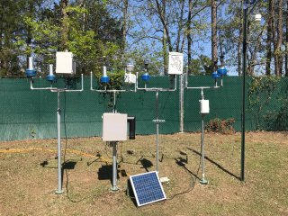 SPods (in blue) are fenceline monitoring devices developed by EPA to measure air pollutant plumes at an industrial facility.  EPA scientists tested them at EPA's research campus in RTP, NC, alongside prototypes designed by commercial developers using the