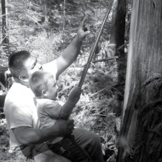 Man and young boy peeling bark from a tree.
